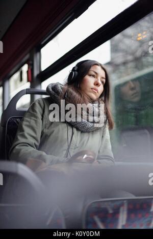 Mädchen mit Kopfhörer auf dem Bus - Stockfoto