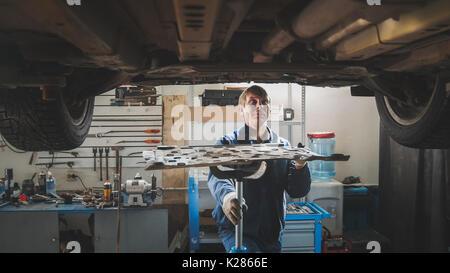 Männliche kaukasischen Arbeiter - Mechaniker im Auto garage Reparatur Werkstatt - unter aufgehoben Auto - Stockfoto