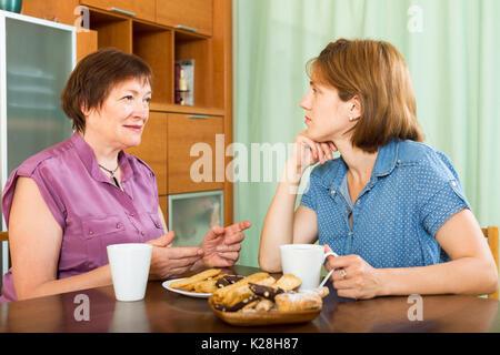 Reife Frau und ihre Tochter Tee-trinken und in einer Diskussion - Stockfoto