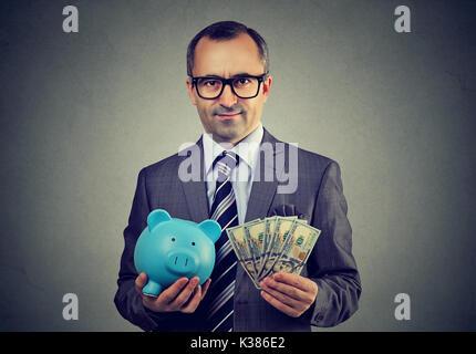 Serious Business Mann mit Sparschwein und Dollar Bargeld Euro-Banknoten - Stockfoto