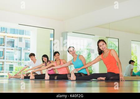 Yoga Klasse in Studio Zimmer, eine Gruppe von Menschen sitzt seitlich nach rechts wirft mit ruhigen Gefühl entspannen, - Stockfoto