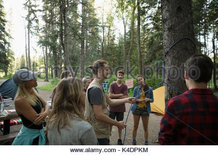 Lehrerinnen und Lehrer Teenager outdoor Schüler von Knoten im Seil um Baum binden auf einem Campingplatz im Wald - Stockfoto
