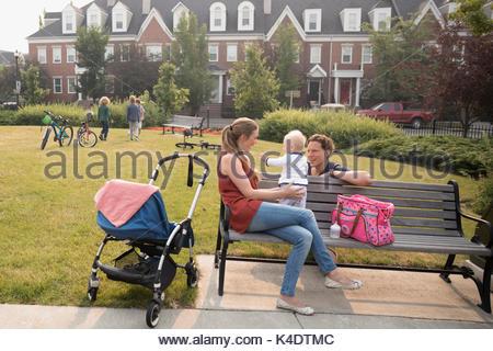 Junge Familie mit Baby sitting auf Nachbarschaft Parkbank - Stockfoto