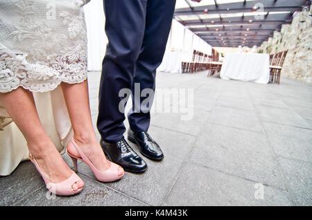 Schuhe des Brautpaares mit Hochzeit Bankett Hintergrund - Stockfoto