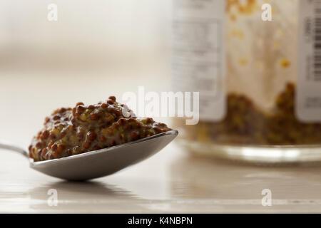 Einen gehäuften Teelöffel vollkorn Senf mit dem Glas Senf jar, die Bestandteil des unscharf Hintergrund. In natürlichem - Stockfoto