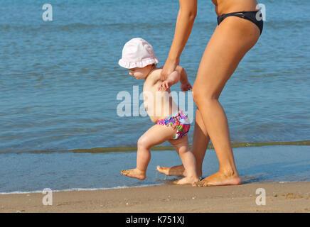 Mama lehrt ihre Tochter an den Strand zu gehen. Erste Schritte mit der Hilfe der Mutter. - Stockfoto
