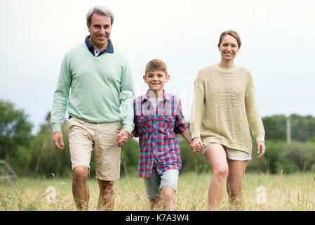 Familie zusammen zu Fuß durch hohes Gras - Stockfoto