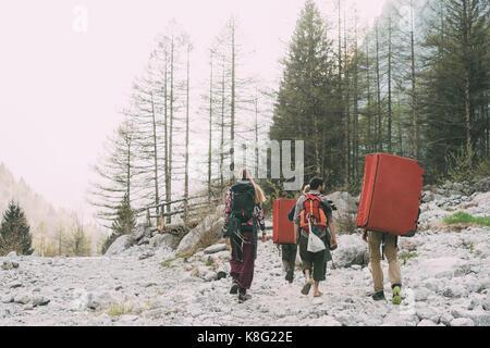 Ansicht der Rückseite des erwachsenen Freunde Wanderungen in Wald mit Rucksack bouldern Matten, Lombardei, Italien - Stockfoto