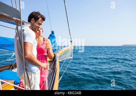 Paar stehend auf dem Boot, auf dem Wasser, Champagnergläser, Anzeigen - Stockfoto