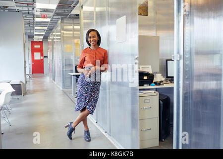 Portrait der Unternehmerin in Büro Flur, lehnte sich gegen Office Surround, lächelnd - Stockfoto