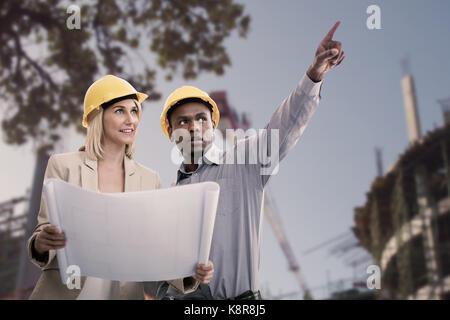 Man Gestik beim Stehen mit weiblichen Architekten gegen niedrigen Winkel der Baustelle - Stockfoto