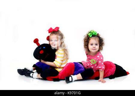 Zwei Schwestern ringen mit einem extra großen gefüllte catepillar. Die beiden Schwestern sitzen auf dem Spielzeug - Stockfoto