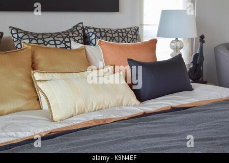 Moderne Schlafzimmer Innenraum mit orange und goldenen Kissen auf dem Bett und Nachttisch Tischleuchte - Stockfoto