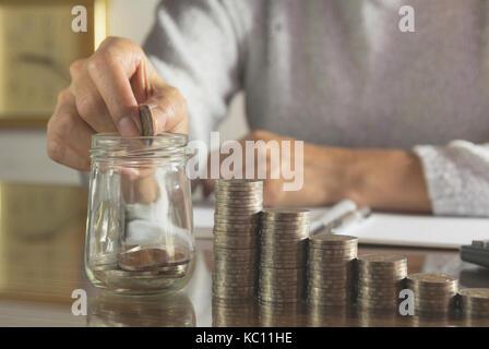 Frau Prozess- und Drop Münze in das Glas mit Stapel Münzen und Rechner. Frau am Tisch. - Stockfoto