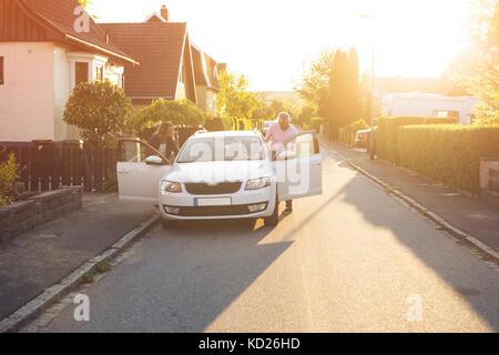 Frau und Mann mit dem Auto in Suburban Area - Stockfoto