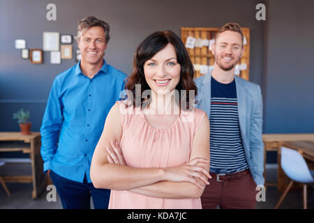 Selbstbewussten jungen Geschäftsfrau mit lachenden Kollegen im Hintergrund stehend - Stockfoto