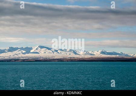 Lake Pukaki mit dem Grünen alpine Bäume und Misty schneebedeckten Berge im Hintergrund, auf der Südinsel von Neuseeland. - Stockfoto
