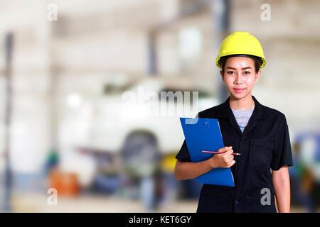 Portrait von lächelnden jungen Mechanikerin Inspektion auf ein Auto in Werkstatt - Stockfoto