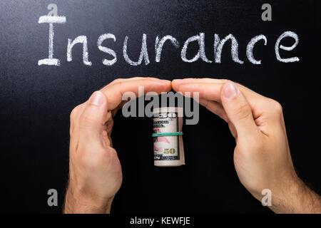 Person schützende Hand gerollt Dollar Banknoten auf der Tafel - Stockfoto