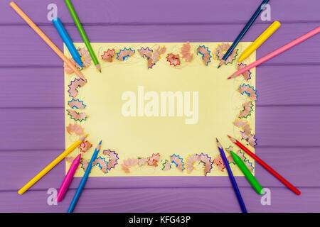 Ein Rahmen aus Buntstift Späne auf ein gelbes Papier - Stockfoto