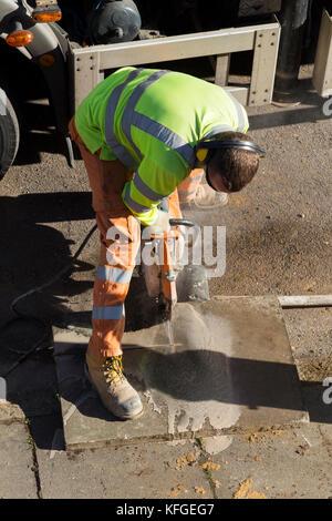Team der Beleuchtung Fremdfirmen Pflaster wieder aufzunehmen und Betonplatten auf Maß geschnitten mit einem Winkelschleifer - Stockfoto