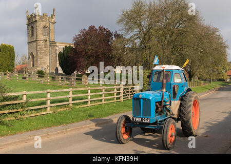 Mann, der alten blauen Oldtimer Traktor durch Dorf Bugthorpe auf Wolds Vintage Gruppe Straße laufen, eine jährliche - Stockfoto