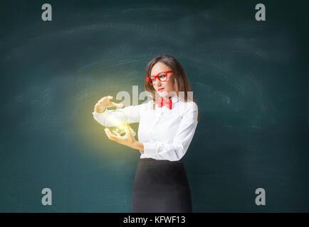 Geschäftsfrau holding Glühbirne vorne auf der Tafel - Stockfoto