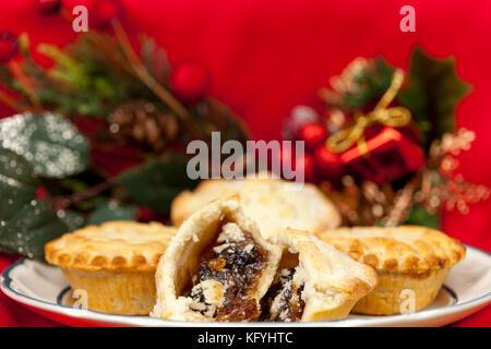 Nahaufnahme eines gebrochenen Mince Pie auf einer Platte mit einigen festlichen Weihnachtsschmuck auf rotem Hintergrund - Stockfoto