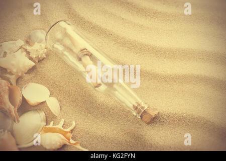 Botschaft in der Flasche am Strand. Sommer Hintergrund mit heißem Sand, im traditionellen Stil - Stockfoto