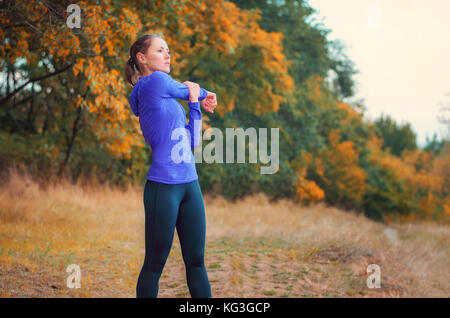 Schönen kaukasischen sportliche Mädchen im blauen Hemd und schwarzen Sport leggins führt Aufwärmen vor dem Joggen - Stockfoto