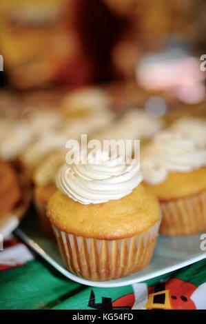 Close-up Frosted, verzierte Cupcakes, vergoldet, auf einem Tisch in einer Gemeinschaft oder Familienfeier. - Stockfoto
