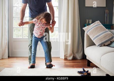 Mädchen Salden zu Fuß auf's Vater Füße zu Hause, nach unten schauen. - Stockfoto
