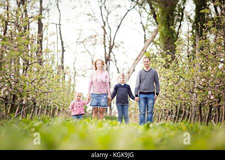 Glückliche junge 4 köpfige Familie zusammen im Freien im Orchard - Stockfoto