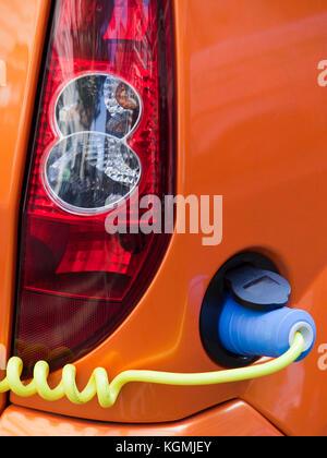 Elektroauto mit einem Ladegerät verbunden über ein Kabel - Stockfoto