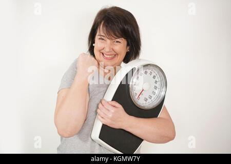 Übergewichtige Frau mit Skala auf weißem Hintergrund - Stockfoto