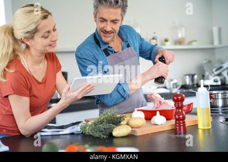 Paar in der Küche zu Hause mit elektronischen Tablet - Stockfoto