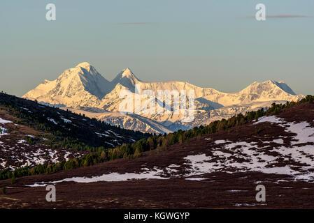 Ausblick Mit der schönen Berge mit Schnee und Gletschern, Pisten mit Schnee bedeckt und spärliche braun Vegetation - Stockfoto