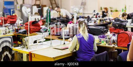 Blonde Frau in der blauen Uniform Herstellung Taschen mit nähmaschine unter der Lampe. Beutel und Klimaanlagen auf - Stockfoto