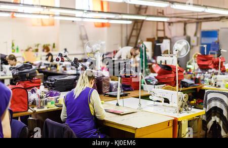 Blonde Frau in der blauen Uniform Herstellung Taschen mit nähmaschine unter der Lampe. Beutel und Klimaanlagen im - Stockfoto