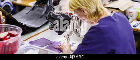 Blonde kurzhaarige Frau in dunkel-blauen Uniform nähen ein lila Geldbörse mit einer Nähmaschine unter der Lampe. - Stockfoto