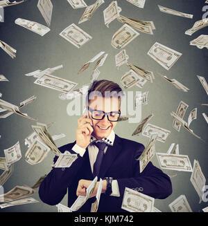 Business Management. busy glücklich Geschäftsmann an Armbanduhr suchen, Gespräch am Handy unter cash Regen. Zeit - Stockfoto