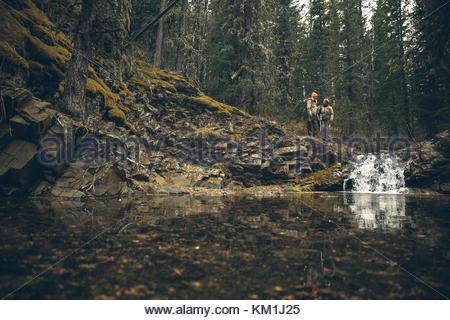 Mutter und Tochter Jäger Jagd über Wasserfall im Wald - Stockfoto