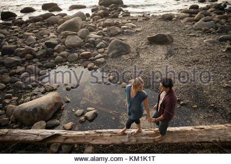Zärtlich Paar halten sich an den Händen und laufen, Balancieren auf log auf felsigen Strand - Stockfoto