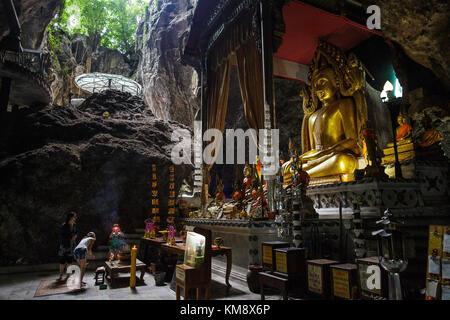 Kanchanaburi, Thailand - 12. Juli 2017: drei Besucher stehen vor einer Buddha-statue im Wat ban Tham Höhlentempel, - Stockfoto