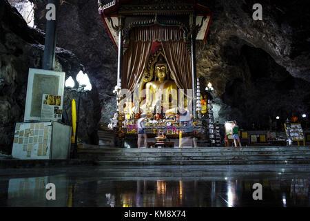 Kanchanaburi, Thailand - 12. Juli 2017: zwei Besucher stehen vor einer Buddha-statue im Wat ban Tham Höhlentempel, - Stockfoto