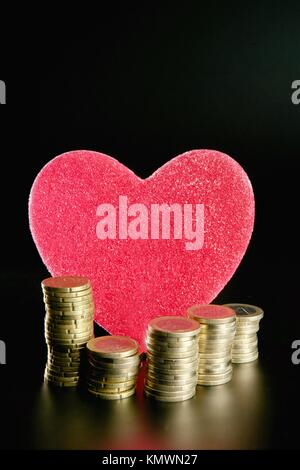 Liebe und Geld Metapher Valentines candy Herz und Euro-Münzen - Stockfoto
