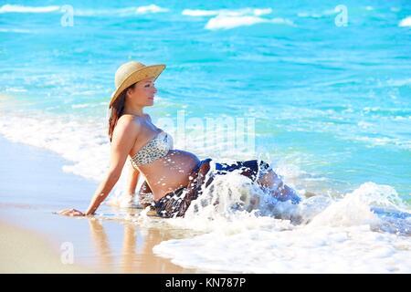 Schwangere Frau am Strand spielen mit Wellen. - Stockfoto