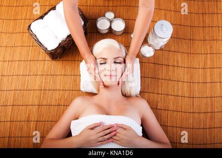Schöne junge Frau entspannende Spa immer therapeutischen Verwöhn-Gesichtsmassage, Verlegung auf Bambus. - Stockfoto