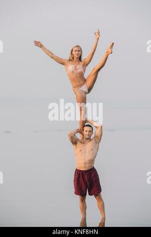 Junges Paar am Strand, Frau auf ein Bein, auf der Schulter des Mannes - Stockfoto