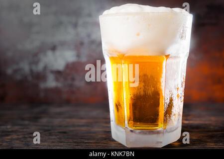 Grosses Glas mit hellem Bier und ein großer Kopf, der Schaum auf alten, dunklen Schreibtisch. Trinken und Getränke - Stockfoto
